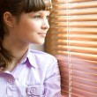 Beautiful girl looks out of the window — Stock Photo
