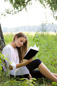 Young girl reading book in park — Stock Photo