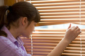 Teenager girl looks out of the window — Stock Photo