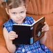 Stock Photo: Little girl reading book and smirk
