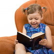 Little girl reading book and have fun - Stock Photo
