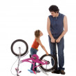Father and daughter inflate wheel bike — Stock Photo #2389162