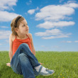 Cute girl sitting on the green grass — Stock Photo #2389178