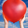 Red balloon in child hands — Stock Photo