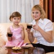 Grandchild and grandmother drink tea - Stock Photo