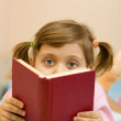 Young girl reading a book on bed — Stock Photo
