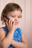 Little girl talking at phone — Stock Photo