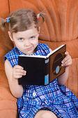 Klein meisje lezen van boek en grijns — Stockfoto