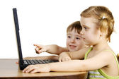 Sister and brother working with a laptop — Stock Photo
