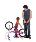 Father and daughter inflate wheel bike — Stock Photo