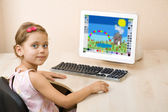 Little girl draws at the computer — Stock Photo