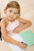 Young girl writing in a notebook — Stock Photo