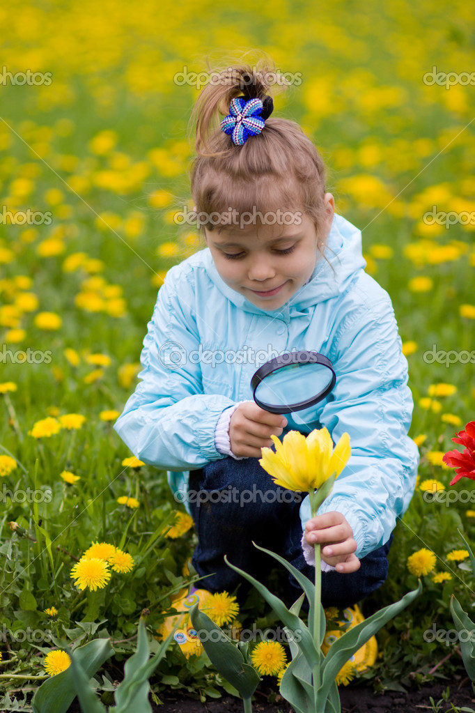 Young girl is looking through a magnifying glass and researching a flower — Stock Photo #2389272