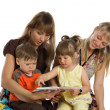 Stock Photo: Two mothers read books to their children