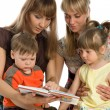 Two mothers read books to their children — Stock Photo #2555294