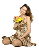 Smiling pregnant brunette with flowers — Stock Photo
