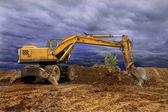 Draga velha cavando a terra, fotografada contra a terra, o céu azul e um arbusto verde — Foto Stock