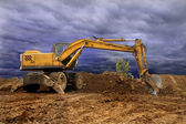 Old dredge digging the earth, photographed against the earth, the blue sky and a green bush — Stock Photo
