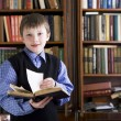 Boy in library holding book — ストック写真