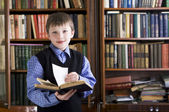 Boy in library holding book — Stockfoto