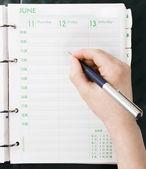 Main qui écrit à un organiseur personnel — Photo