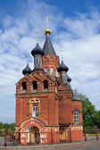 Red Church with black cupolas — Stock Photo