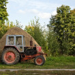 Old tractor and haystack - Stock Photo