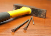 The hammer, nails lie on a wooden table — Stock Photo