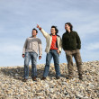 Three casual young men at the beach - Stock Photo