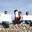 Stock Photo: Men Holding White Card at the beach