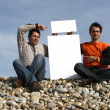 Men Holding White Card at the beach — Foto de Stock