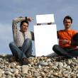 uomini tenendo scheda bianca in spiaggia — Foto Stock