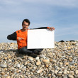 Man Holding White Card at the beach - Stock Photo