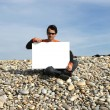 Man Holding White Card at the beach — Stock Photo #1483090