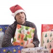 Royalty-Free Stock Photo: Young Man in Santa hat, full of gifts