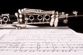 Clarinet isolated over sheet music — Stock Photo