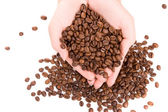 Woman hands full of coffee beans — Stock Photo