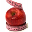 Tape measure wrapped around the apple - Stock Photo