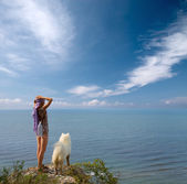 Girl and dog standing on precipice — Stock Photo