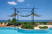 Couches and sunshade on the sea coast — Stock Photo