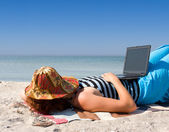 Girl sleep with laptop at sea beach — Stockfoto