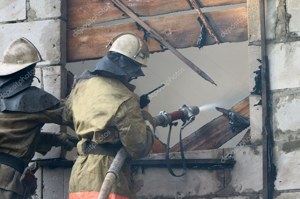 Firefighter with firehose spraying water in window of flaming house — Stock Photo #1495662