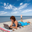 Girl with laptop at sea shore — Stock Photo #1507495