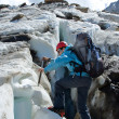 Backpacker woman with ice-axe climbing — Stockfoto