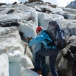Backpacker woman with ice-axe climbing — Stok fotoğraf
