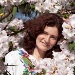 Smiling girl in flowering bush — Stock Photo #1508194