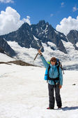Smiling backpacker woman with ice-axe — Stock Photo