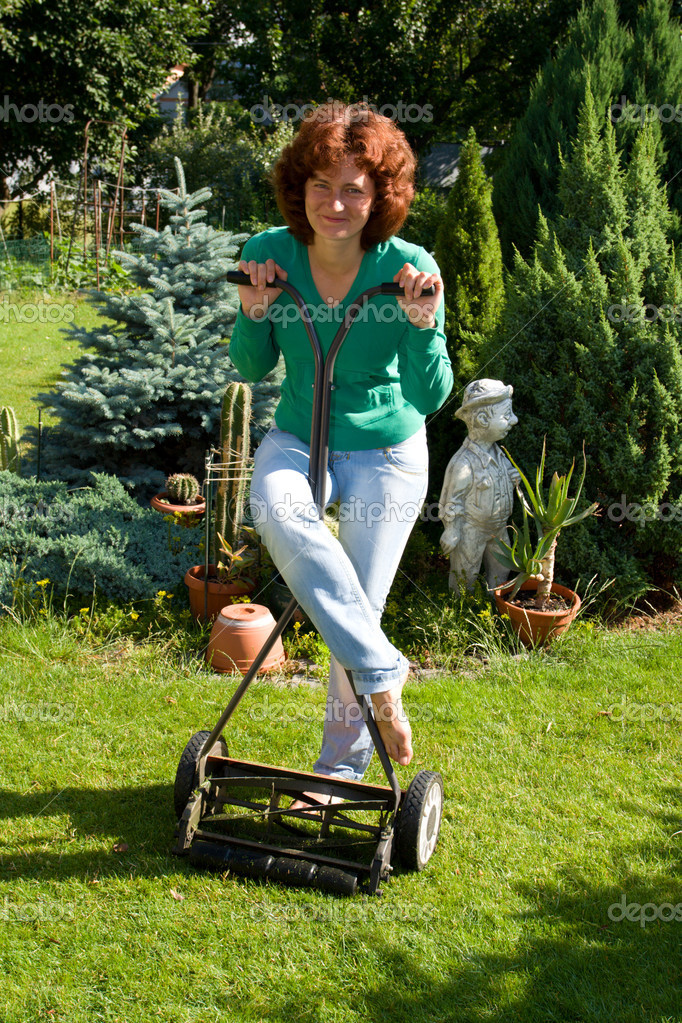 Girl with lawn mower in her garden  Stock Photo #1507212