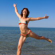 Happy smiling girl jumping at sea beach — Stock Photo #1520479