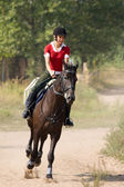 Woman riding horseback — Stock Photo